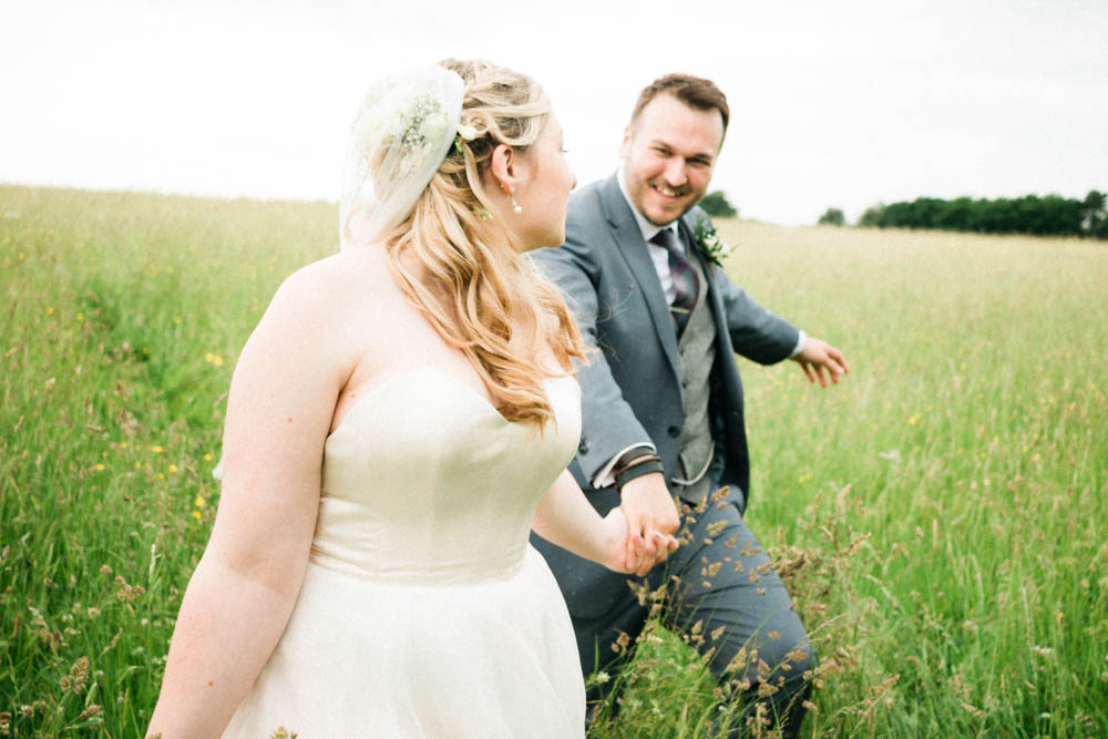 Special-Day-Photography-Cripps-Barn-Cirencester-Gloucester-Barn-Wedding-bride-and-groom-walk-through-a-field-together.jpg
