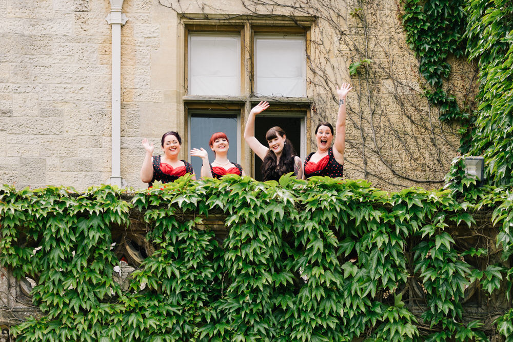 Special-Day-Photography-Manor-By-The-Lake-Cheltenham-Manor-By-The-Lake-50s-Wedding-Bridesmaids-wave-from-a-balcony.jpg