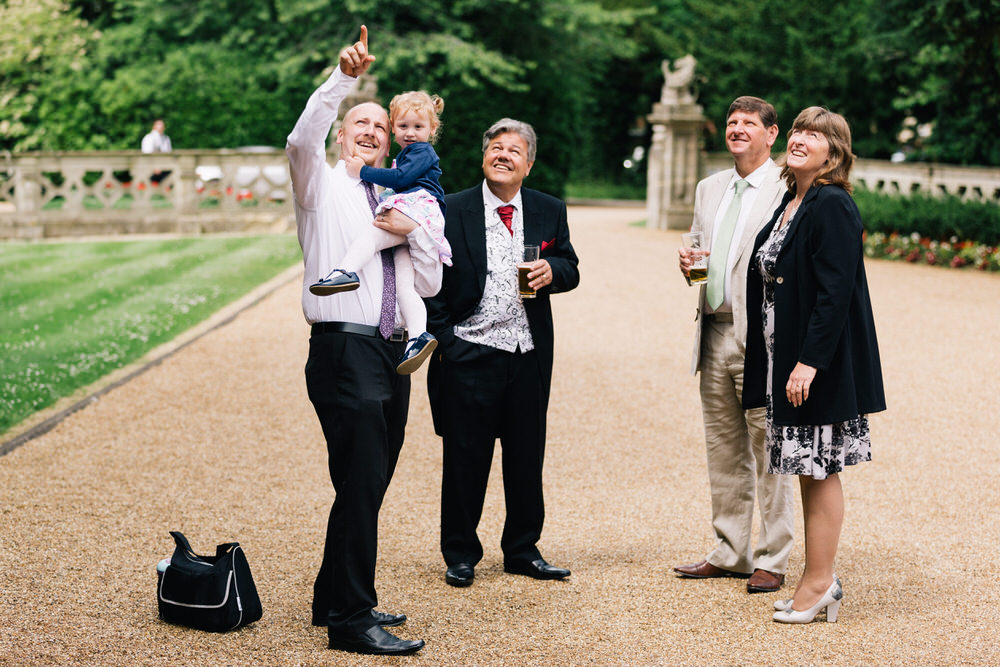Special-Day-Photography-Manor-By-The-Lake-Cheltenham-Manor-By-The-Lake-50s-Wedding-Guests-pointing-upwards.jpg
