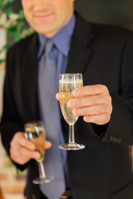 Special-Day-Photography-Prestbury-WI-Hall-Cheltenham-Prestbury-Church-Wedding-a-guest-offers-champagne.jpg