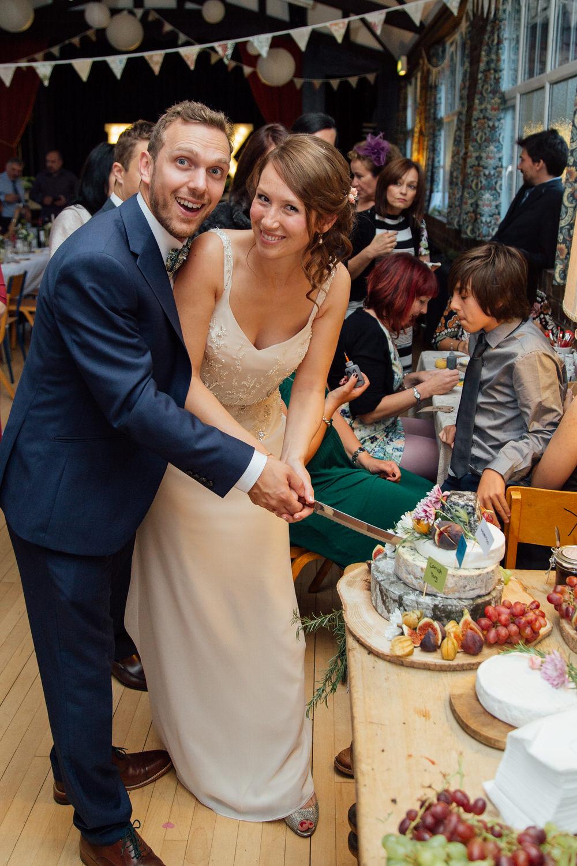 Special-Day-Photography-Prestbury-WI-Hall-Cheltenham-Prestbury-Church-Wedding-cutting-a-cheese-cake.jpg