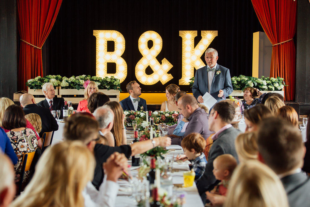 Special-Day-Photography-Prestbury-WI-Hall-Cheltenham-Prestbury-Church-Wedding-father-of-the-bride-speeches-with-illuminated-letters-on-stage.jpg