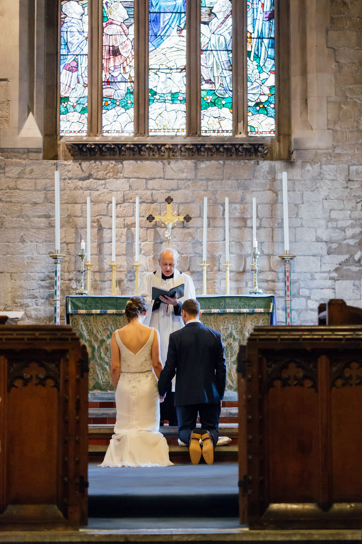 Special-Day-Photography-Prestbury-WI-Hall-Cheltenham-Prestbury-Church-Wedding-kneeling-in-a-church-for-the-blessing-during-a-wedding.jpg