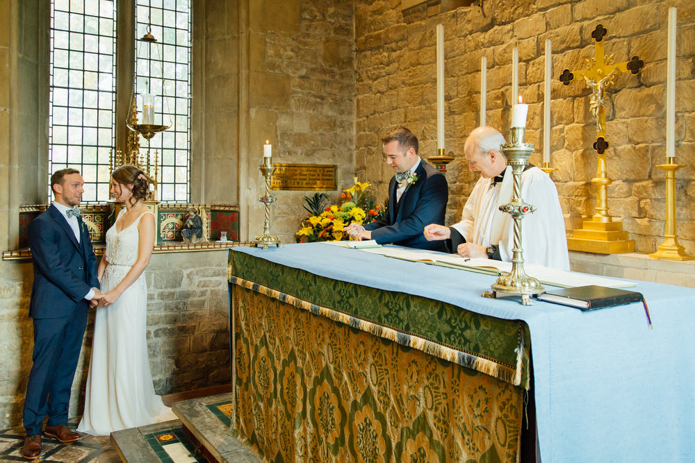 Special-Day-Photography-Prestbury-WI-Hall-Cheltenham-Prestbury-Church-Wedding-the-bride-and-groom-wait-whilst-the-witnessess-sign-the-registry-books.jpg