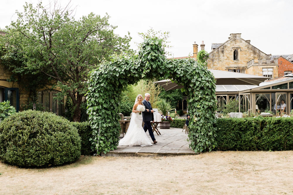 Special-Day-Photography-The-Manor-House-Hotel-Moreton-in-Marsh-Moreton-In-Marsh-Summer-Wedding-Bride-and-father-of-the-bride-walking-under-flower-arches-in-a-garden.jpg