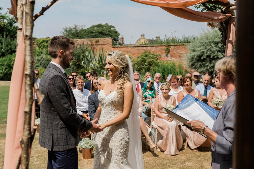 Special-Day-Photography-The-Manor-House-Hotel-Moreton-in-Marsh-Moreton-In-Marsh-Summer-Wedding-Bride-and-groom-exchanging-vows-in-the-summer-sun-outdoors.jpg