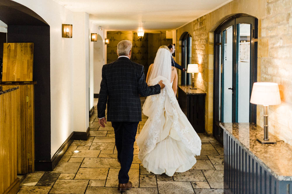 Special-Day-Photography-The-Manor-House-Hotel-Moreton-in-Marsh-Moreton-In-Marsh-Summer-Wedding-Father-of-the-bride-and-bride-walking-through-Manor-House-Hotel.jpg