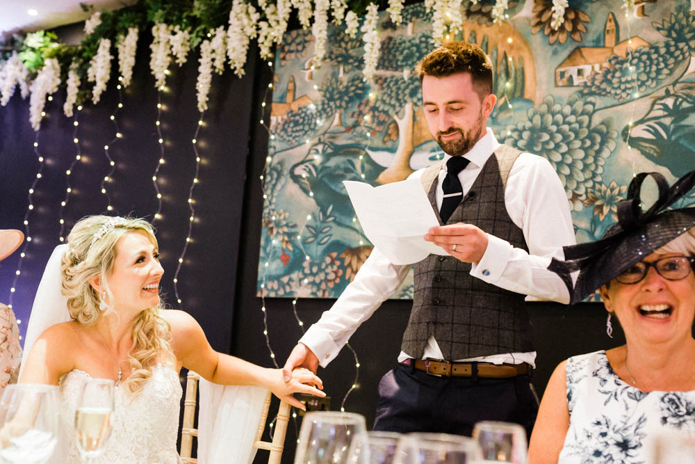 Special-Day-Photography-The-Manor-House-Hotel-Moreton-in-Marsh-Moreton-In-Marsh-Summer-Wedding-The-groom-makes-speeches-with-his-bride.jpg