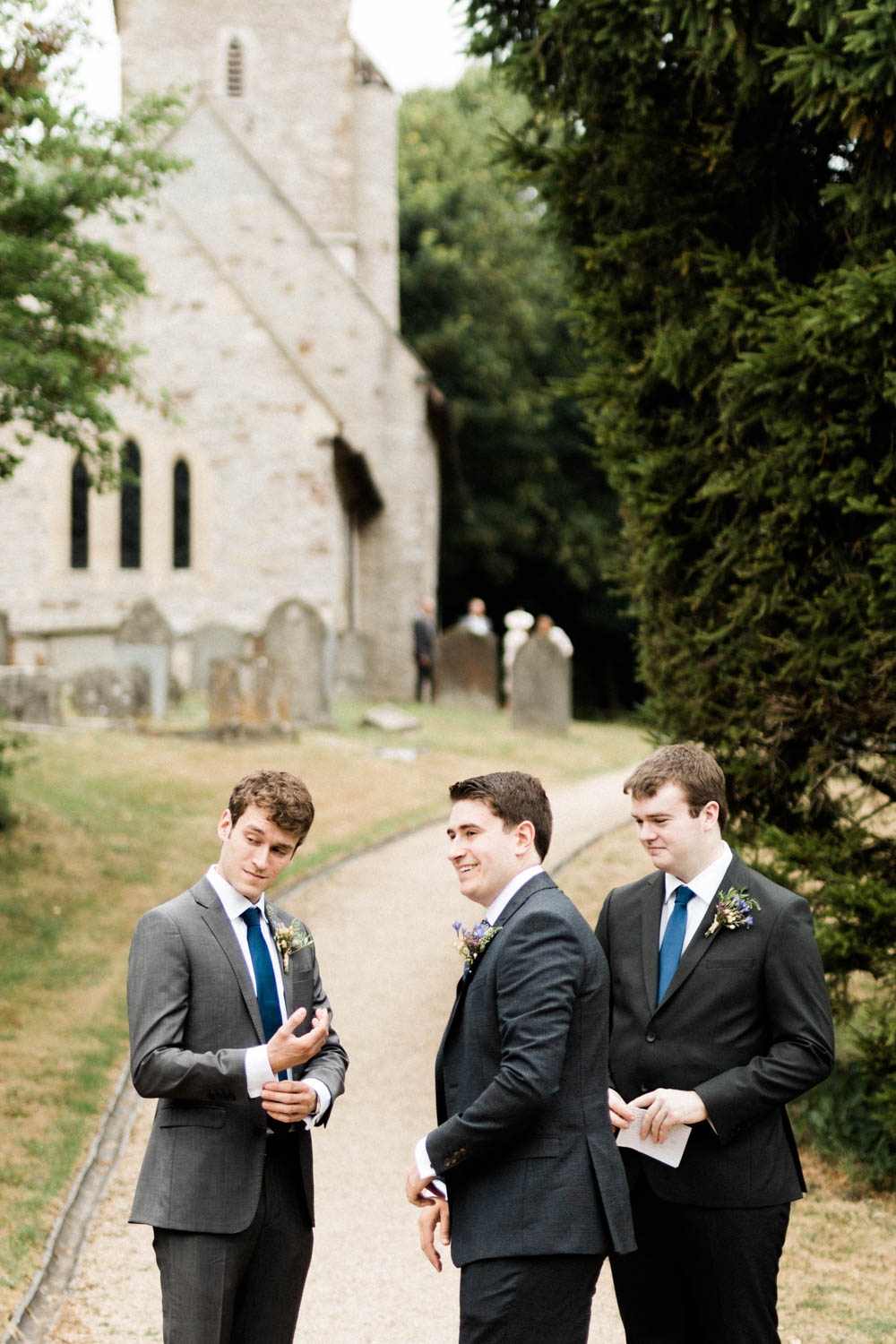 Special-Day-Photography-Hellens-Manor-Much-Marcle-Tudor-Manor-Wedding-the-groomsmen-wait-for-guests-outside-a-church.jpg