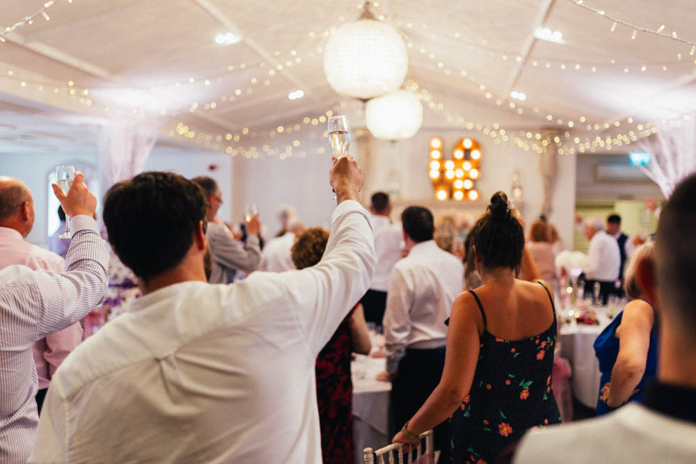Special-Day-Photography-Manor-By-The-Lake-Cheltenham-Cheltenham-Manor-Wedding-crowd-cheers-for-a-speech.jpg