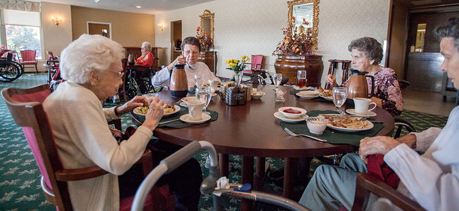 Several Senior Residents Enjoying Breakfast Together in the Dining Room.