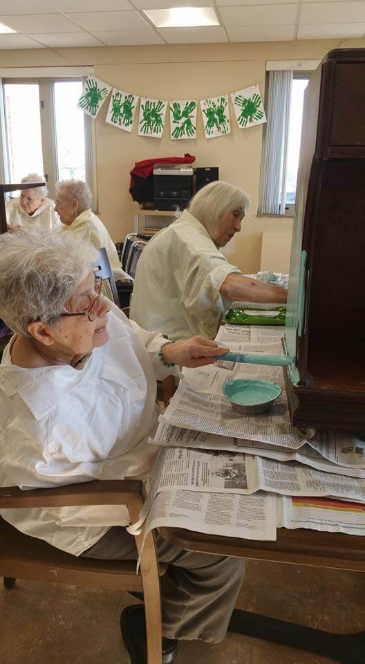 Residents enjoying painting furniture class at St. Louis Altenheim.