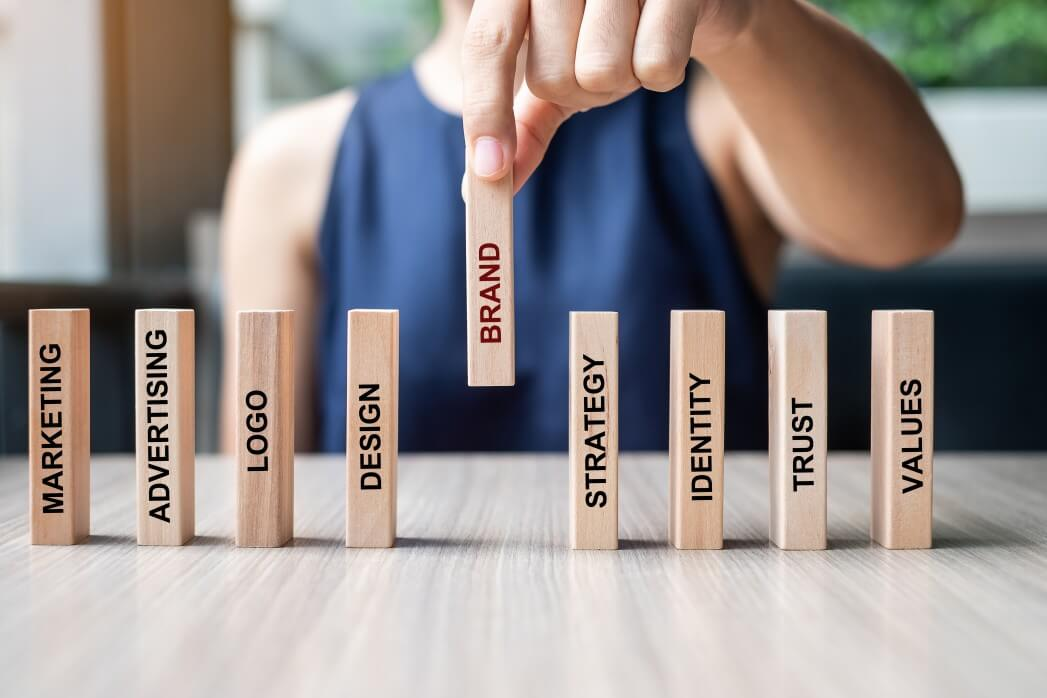 businesswoman-hand-placing-or-pulling-wooden-dominoes-with-brand-text-and-marketing-advertising-logo_t20_YwXeLX.jpg