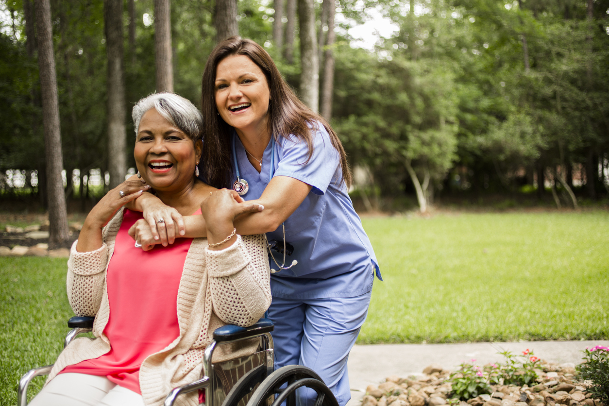 Black Lady in Wheelchair with nurse hugging.jpg