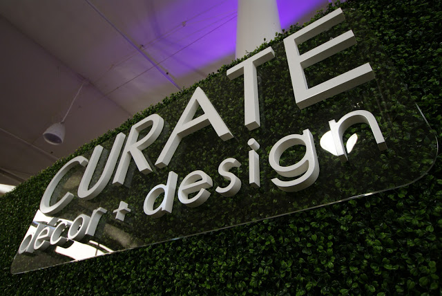 3-D logo mounted against our hedge-wrapped booth