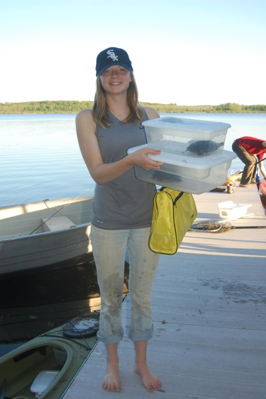 Smiling researcher holding bins with individual turtles