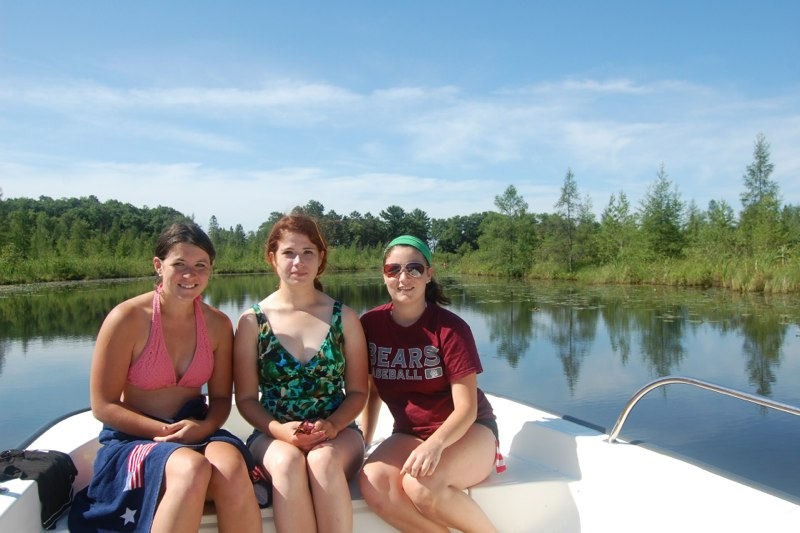 Three female researchers sitting at the bow of a boat
