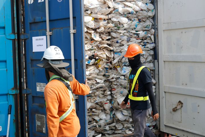 ASSOCIATED PRESS  Workers open a container full of non-recyclable plastic detained by authorities at the west port in Klang, Malaysia.