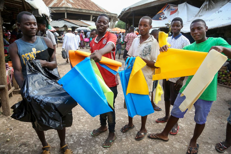 A Tanzanian hawker (L) sells plastic bags, while others present new alternative bags at the local market in Dar es Salaam on May 31 2019. Picture: AFP/ SAID KHALFAN