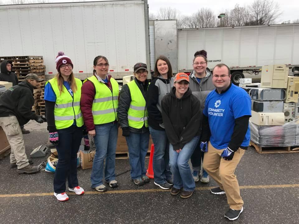 L to R: Tiffany Mathon, Jessica Blackwell, Julia Copp, Jen Hogan, Natalie Michaud, Ashley Ward and Matthew Shaw, volunteers from Community Credit Union unloading vehicles at Recycle Day 2018.