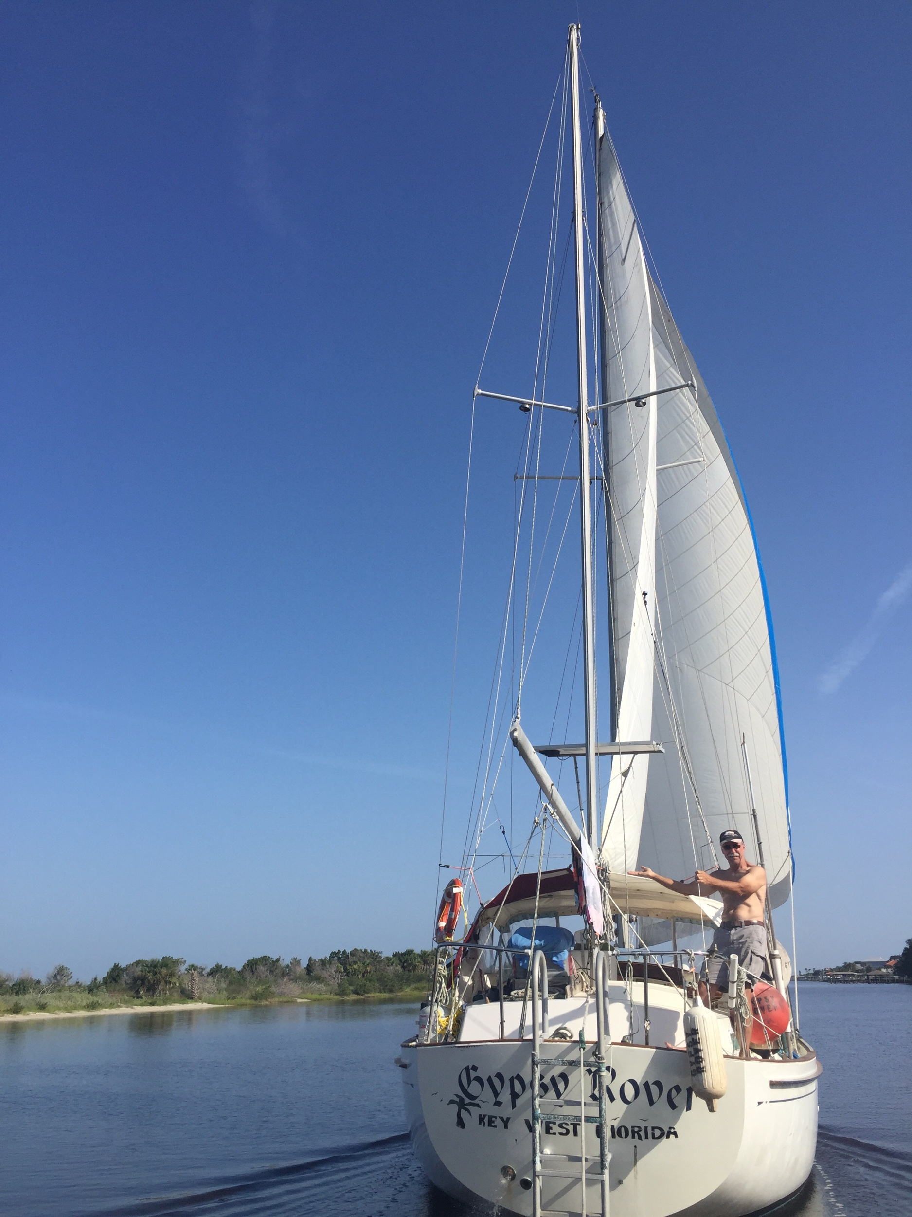 First mate, Grandpa Mike, near Merritt Island, FL trimming some sails while traveling north on the ICW.