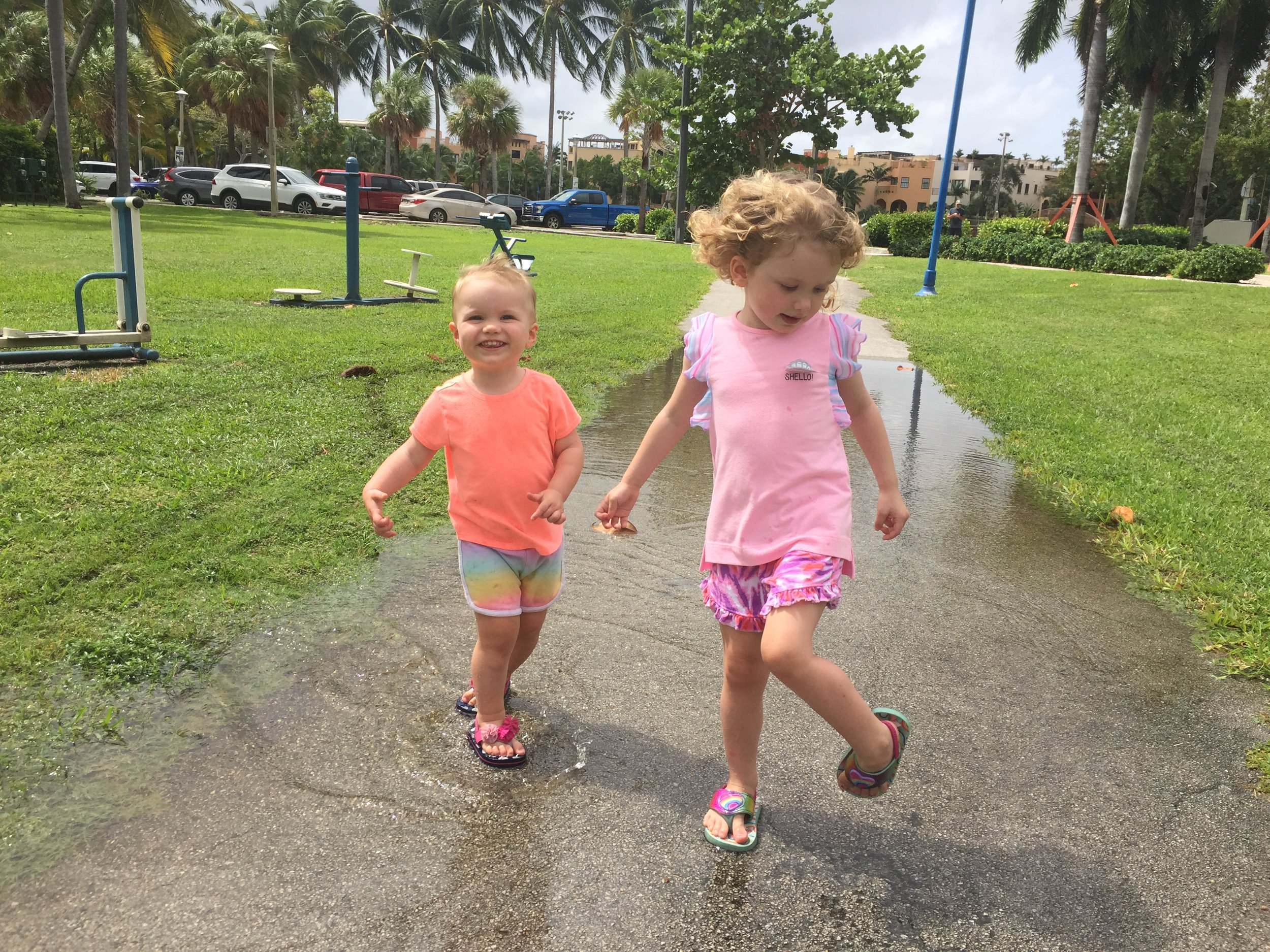 Making the most out of the rainy days; Abby teaching Hadley one of her favorite pastimes, puddle jumping, in Coconut Grove, FL.