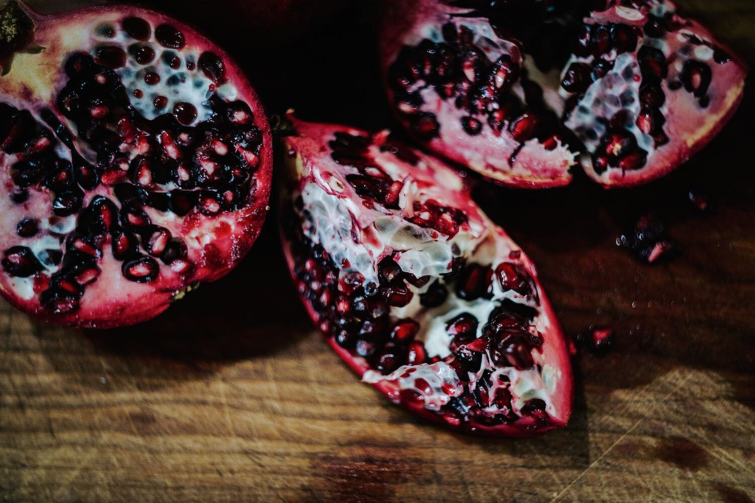 Cut open pomegranates on a wood table