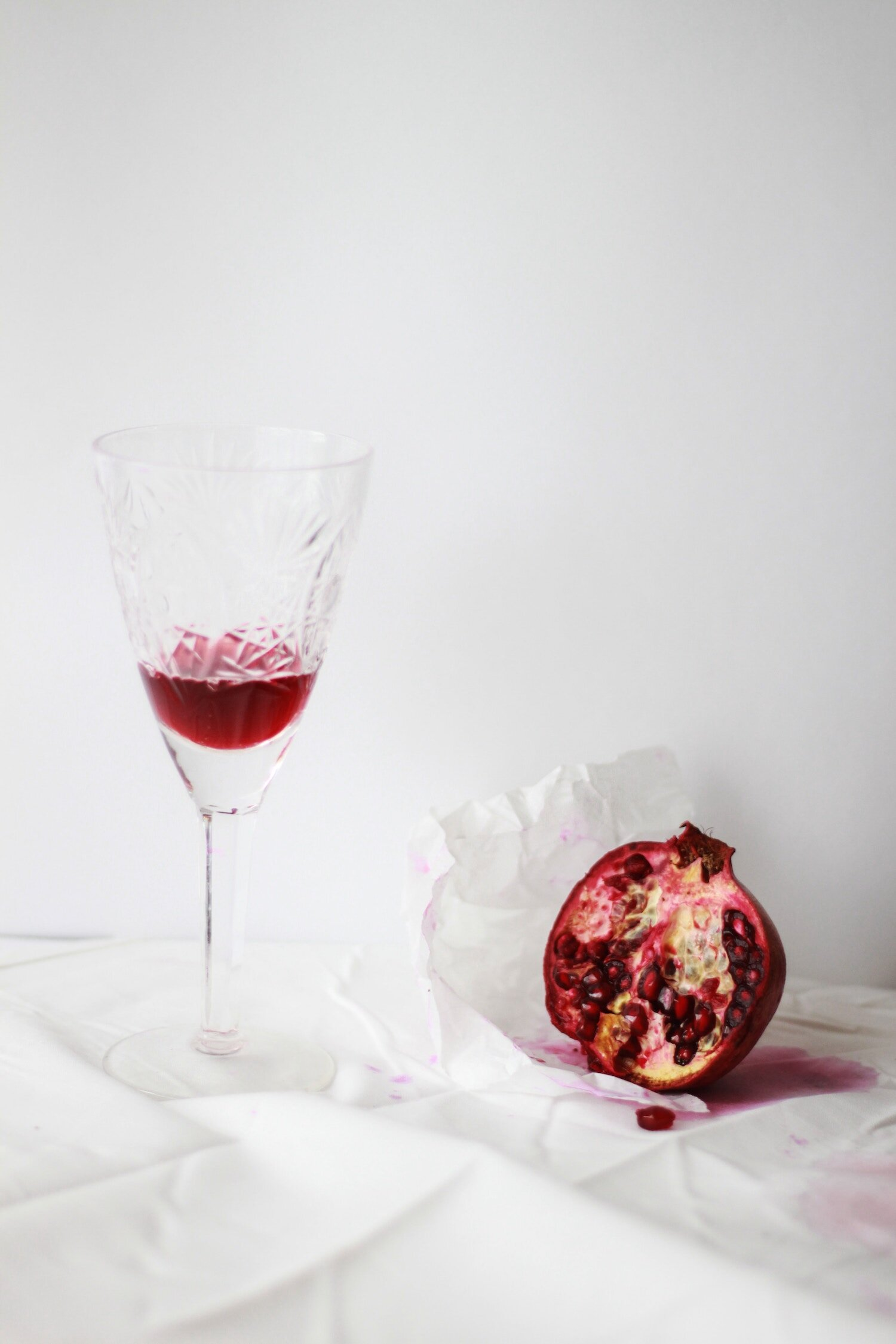 A pomegranate fruit with a crystal glass of juice on a white background