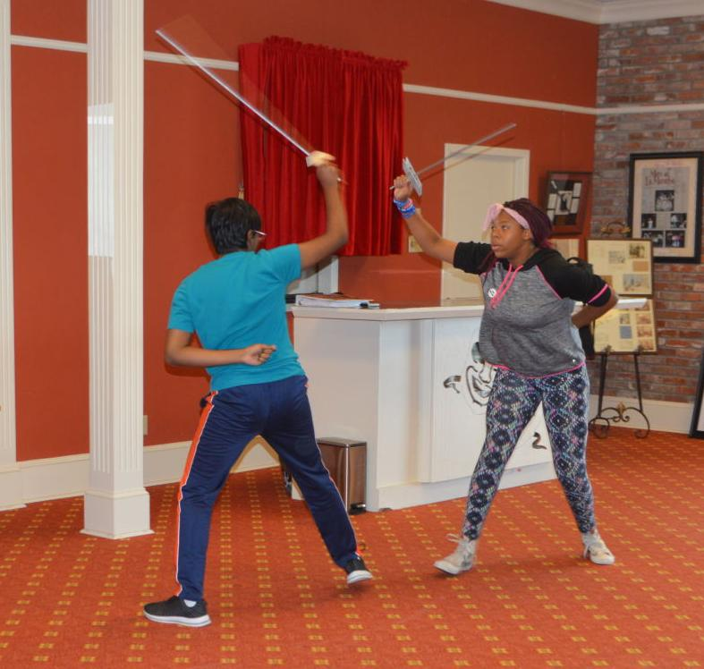 "Raghav Nallani, left, and Niobi Elliott rehearse a sword fight that will be featured in the upcoming ""Shakespeare Scene Fest."""