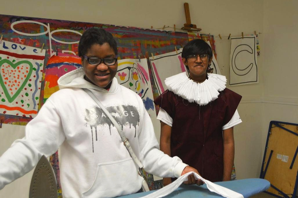 "Nayia Elliott, left, works on making the Elizabethan ruffle shirt collars that will be worn in the upcoming ""Shakespeare Summer Scene Fest."" Raghav Nallani models the finished product."