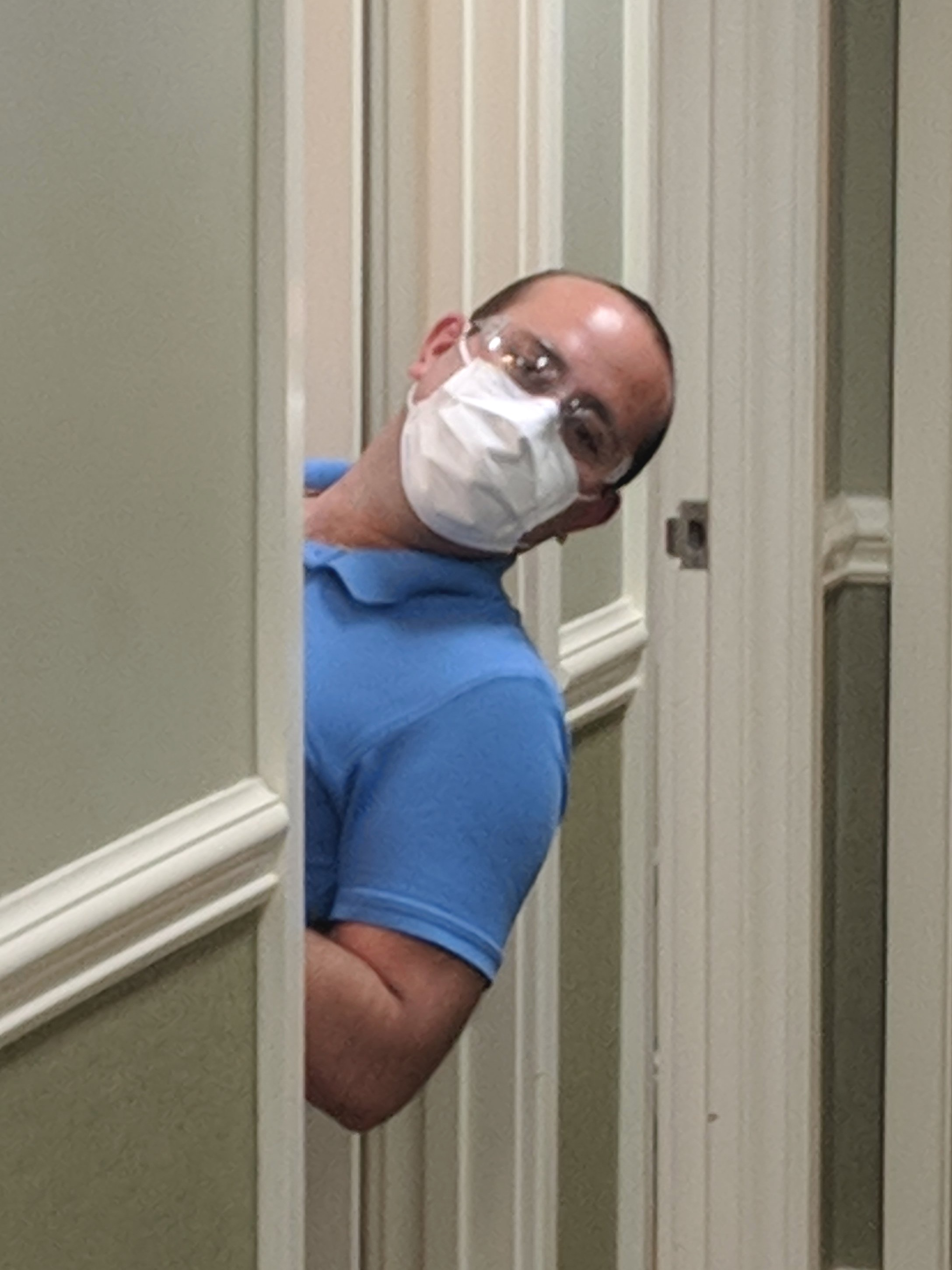 Dr. Ben Dunlap  sticking his head out of the door to the exam room with a mask on and safety googles at Whole Life Dental. Dentist office can be found in Greenwood, South Carolina. Whole Life Dentist is a Affordable dentist greenwood south Carolina
