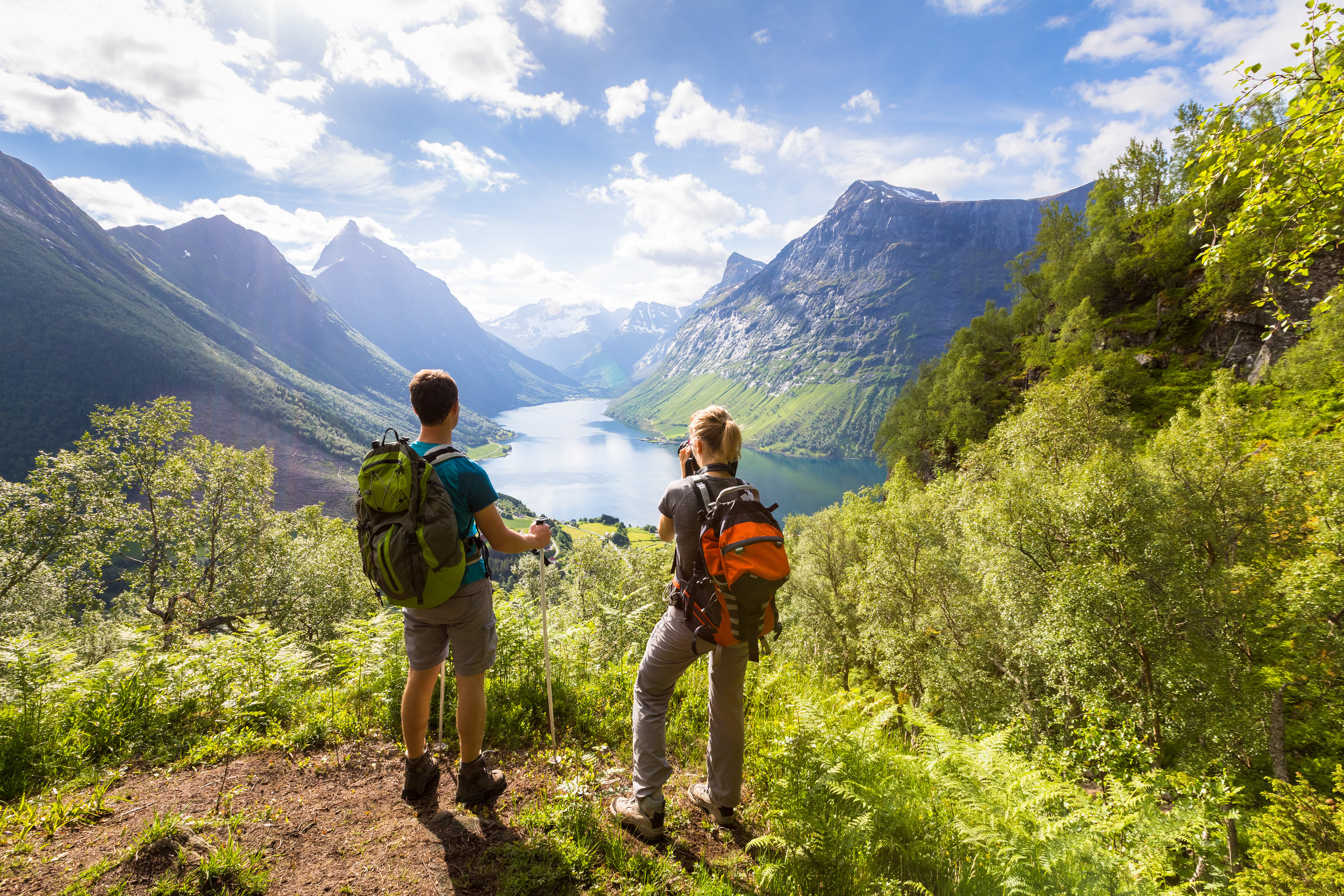 Two-hikers-at-viewpoint--in-mountains-with-lake,-sunny-summer-814397912_4800x3200.jpeg