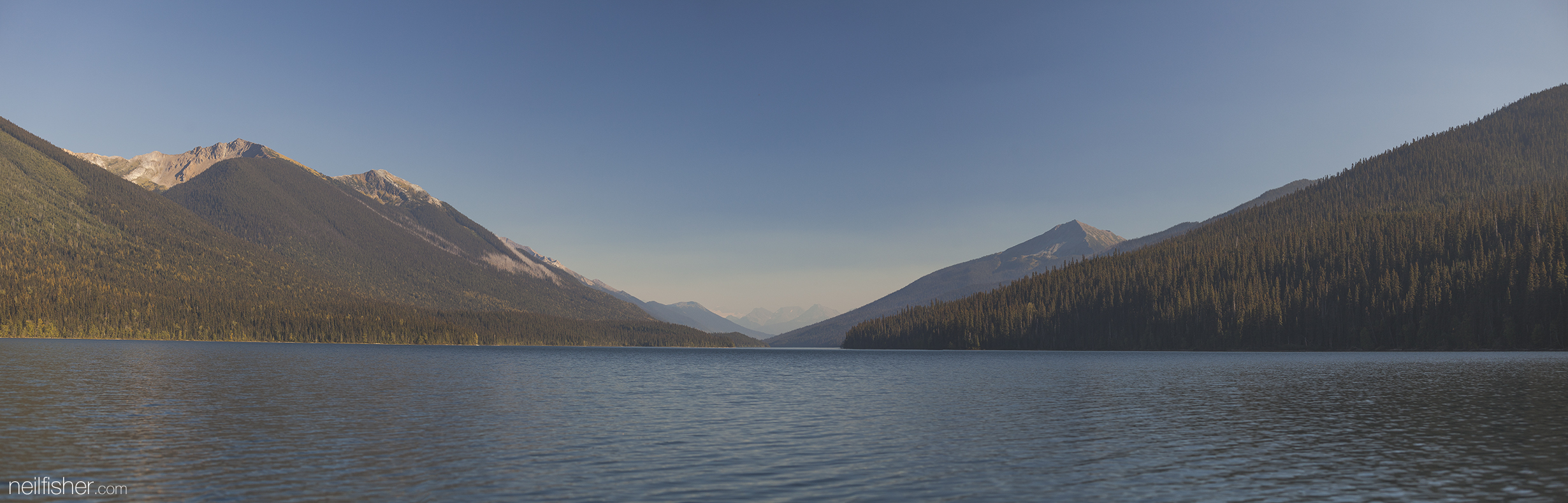 Four photos stitched together looking south down the main arm of Isaac, taken from in the canoe where the two arms intersect. The most predominant rocky peaky on the right side of the lake is  Mount Faulkner , low in the centre are the Caribou Mountains, the far left rocky peak is Mount Amos Bowman, and to the right of Mount Amos Bowman is Vixen Peak. EXIF 1/400 f/4.0 ISO200 70mm