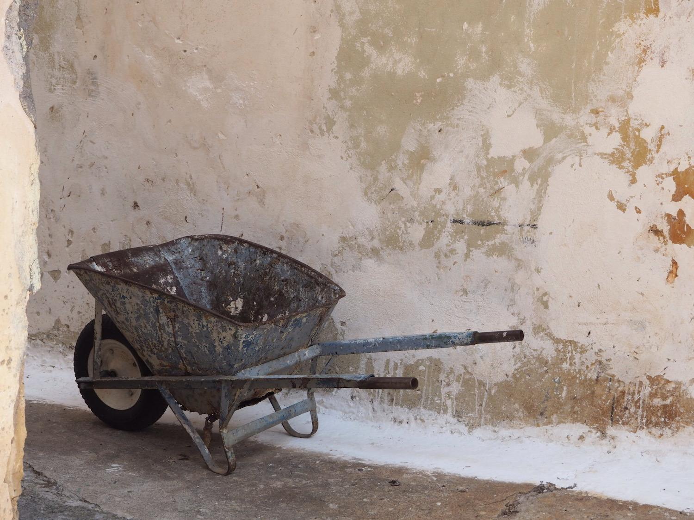 somewhere in Greece, a wheelbarrow by a wall