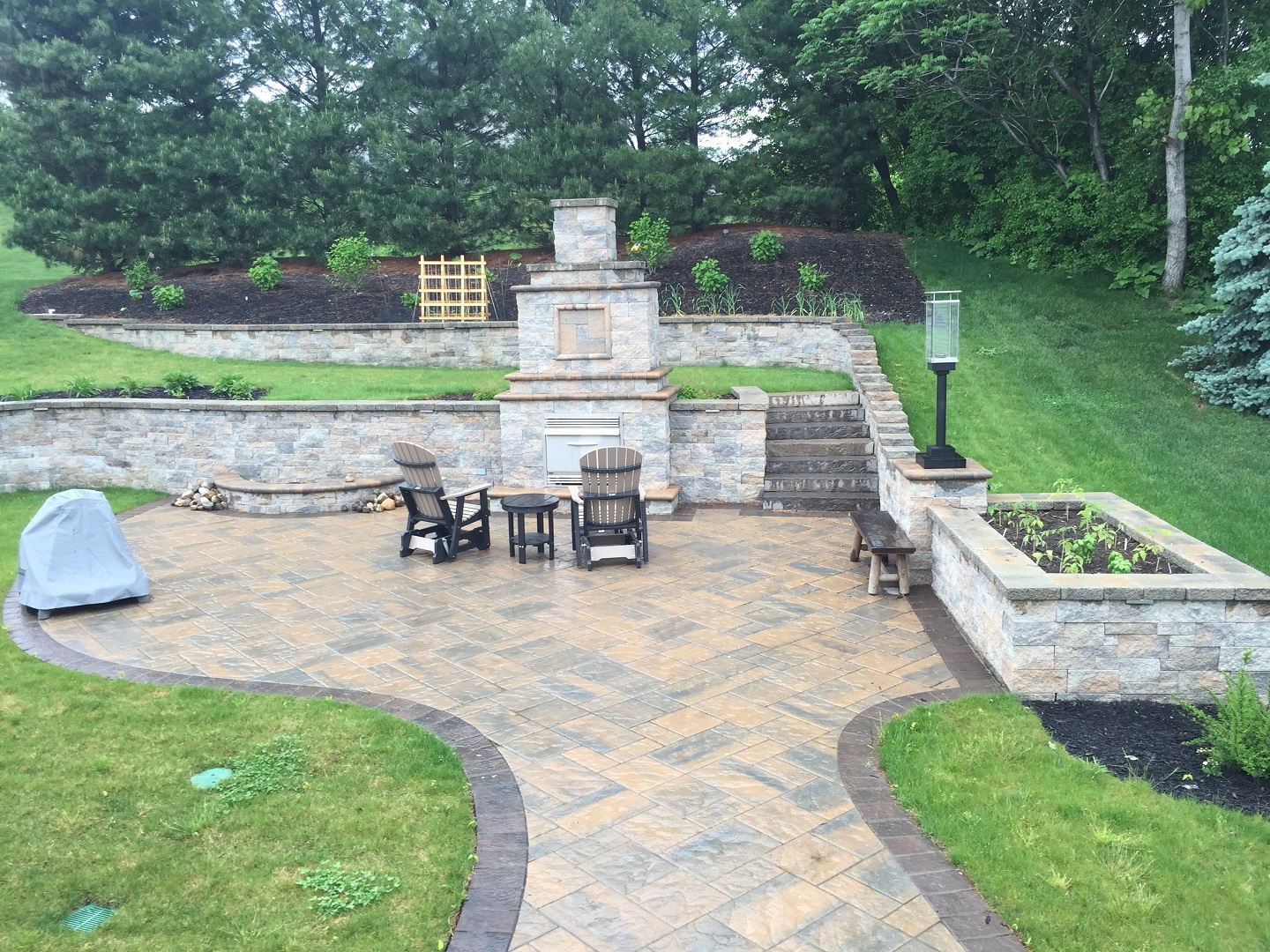 Patio with outdoor fireplace and retaining wall in Halfmoon, NY