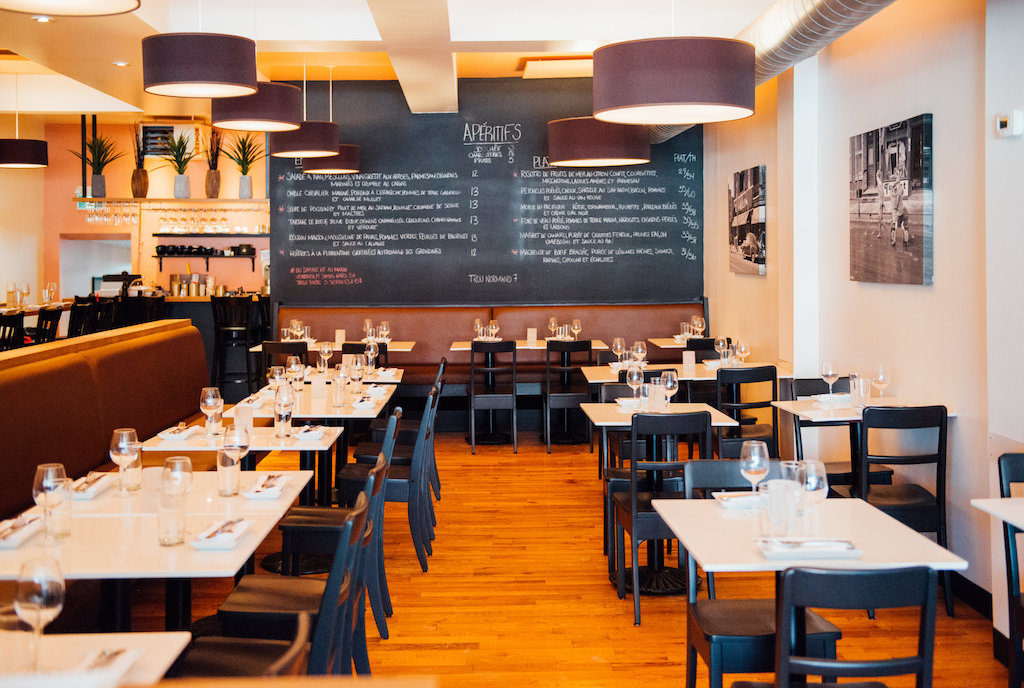 La salle à manger… - La salle à manger de 75 places, à la fois chic et décontractée, est éclairée par une série de luminaires circulaires qui baignent la salle d'un éclairage chaleureux. Plusieurs petites tables pour deux viennent entourer une banquette centrale; cette dernière ajoute une profondeur au restaurant et guide le regard vers la grande ardoise du restaurant, sur laquelle on peut lire le menu. Des photos noir et blanc grand format de l'équipe de crosse de Verdun, du Natatorium, et des scènes de la vie quotidienne des Verdunnois au siècle dernier habillent les murs de la salle à manger.