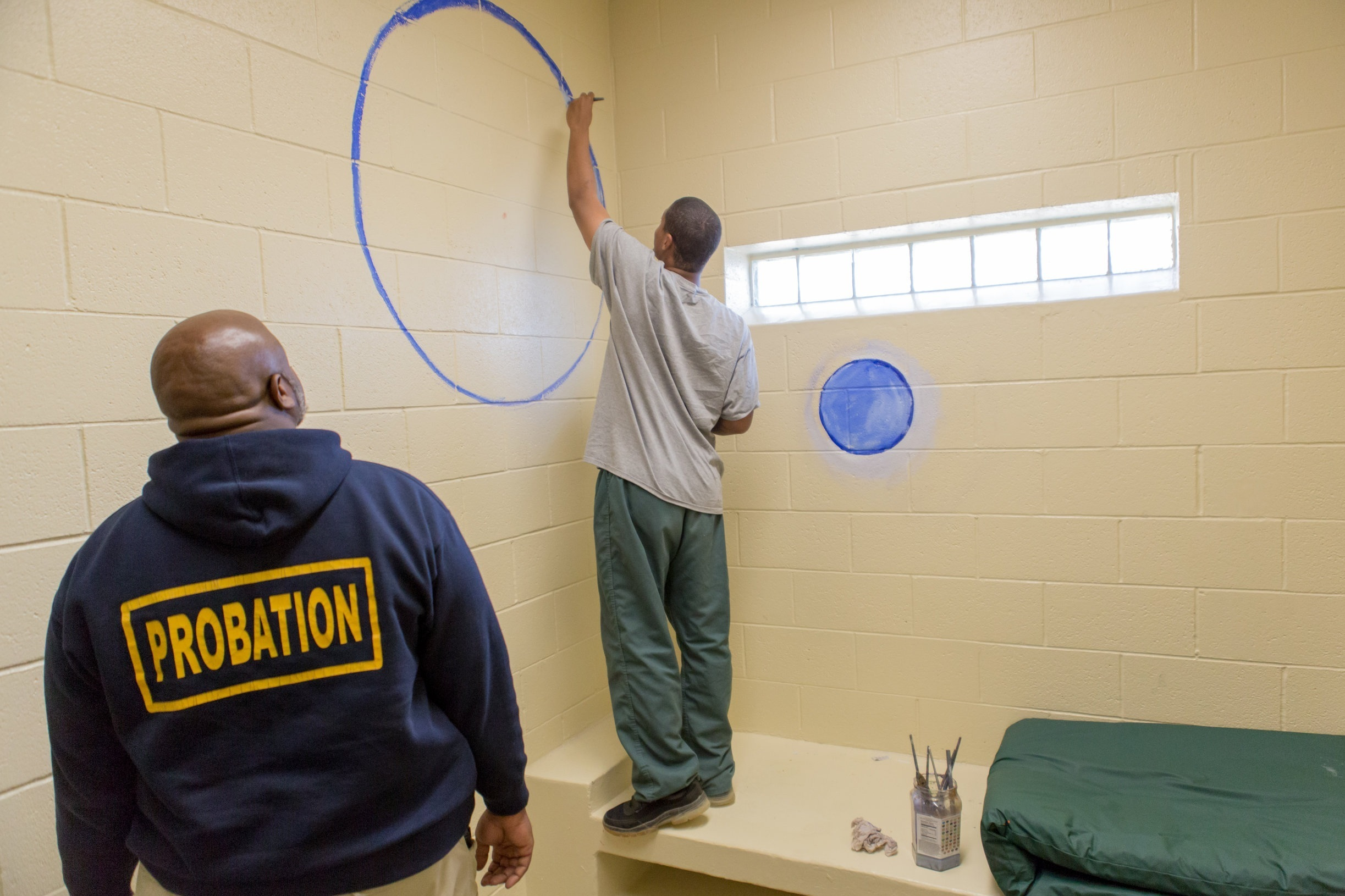 Student transforms a solitary cell into a mediation room while Probation looks on. And after completion.  Photo Credit: Cam Sanders