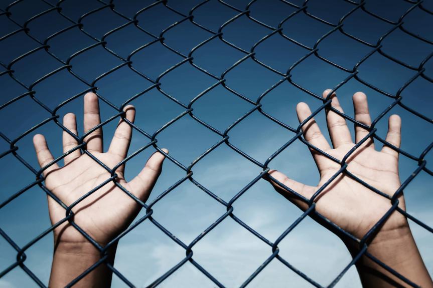 AIYN Youth Hands behind gate.jpg
