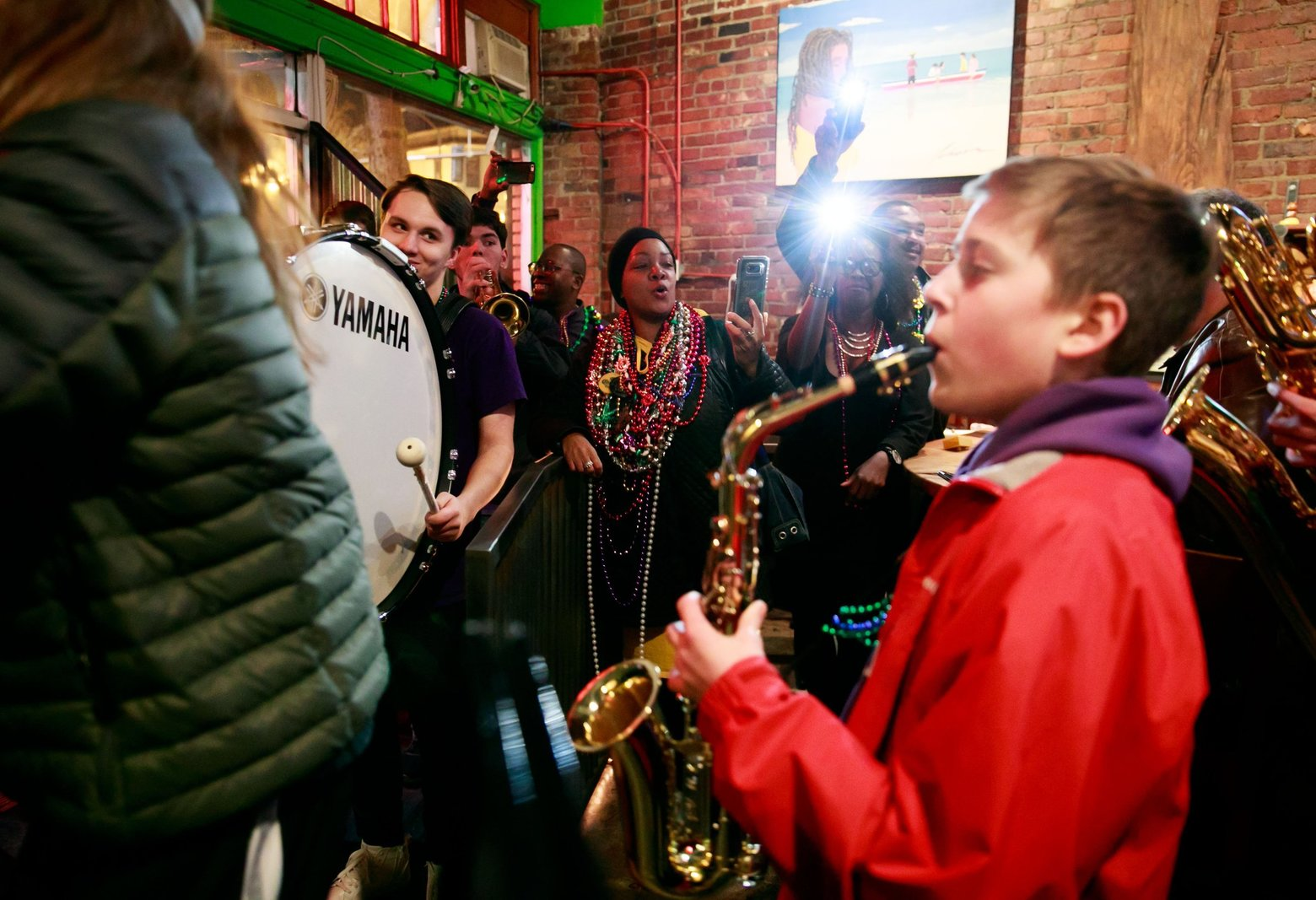 Columbia City Beatwalk lead organizer Tish Gallow, center, cheers on the Garfield High School Marching Band during 2018's Fat Tuesday edition of the longstanding neighborhood music crawl.