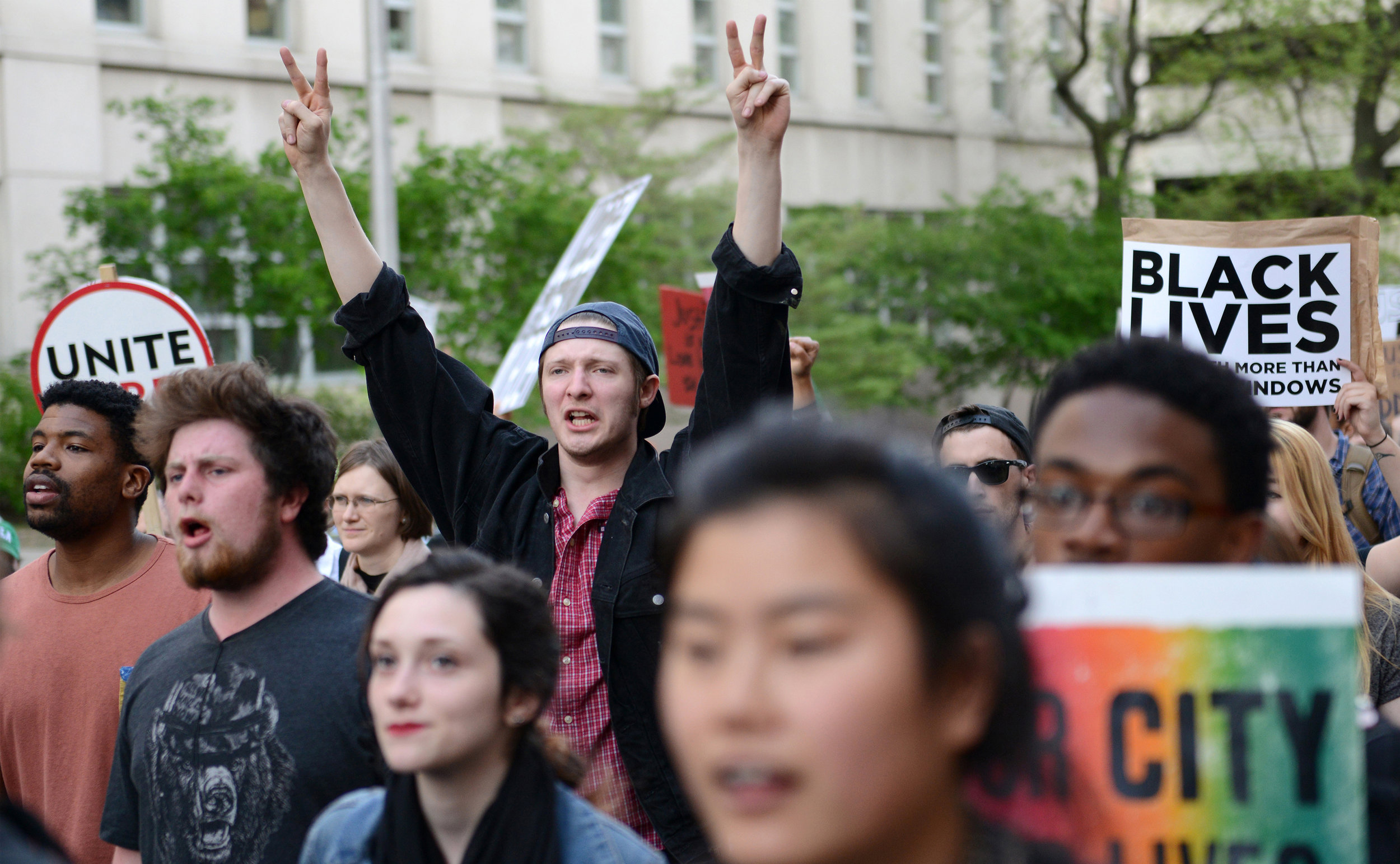 Protester Renato Flores holds up peace signs on Wednesday, April 29, 2015 in Baltimore, Md. as Baltimore residents march from City Hall to Penn Station in a peaceful protest of the death of Freddie Gray. The march took place two days after violent protests broke out in the streets of Baltimore. Photo by David Andrews.