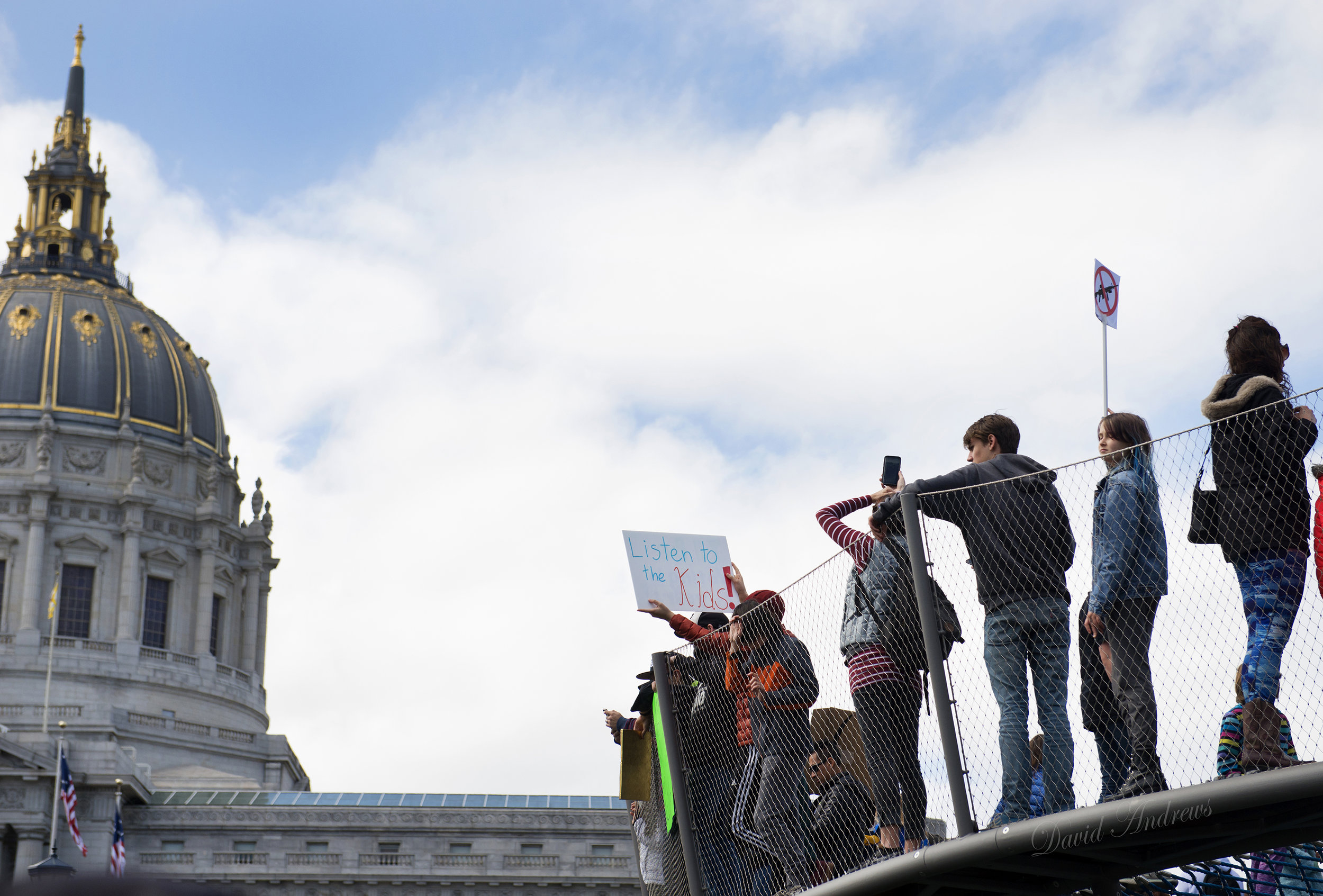 """A protester holds a """"Listen to the kids"""" sign while standing on playground equipment outside City Hall during the 'March for our Lives' demonstration in San Francisco, Ca. on Saturday, March 24, 2018. The gathering in San Francisco was one of many marches nationwide to advocate for voter registration in an effort to vote to curb US gun laws. Photo by David Andrews."""