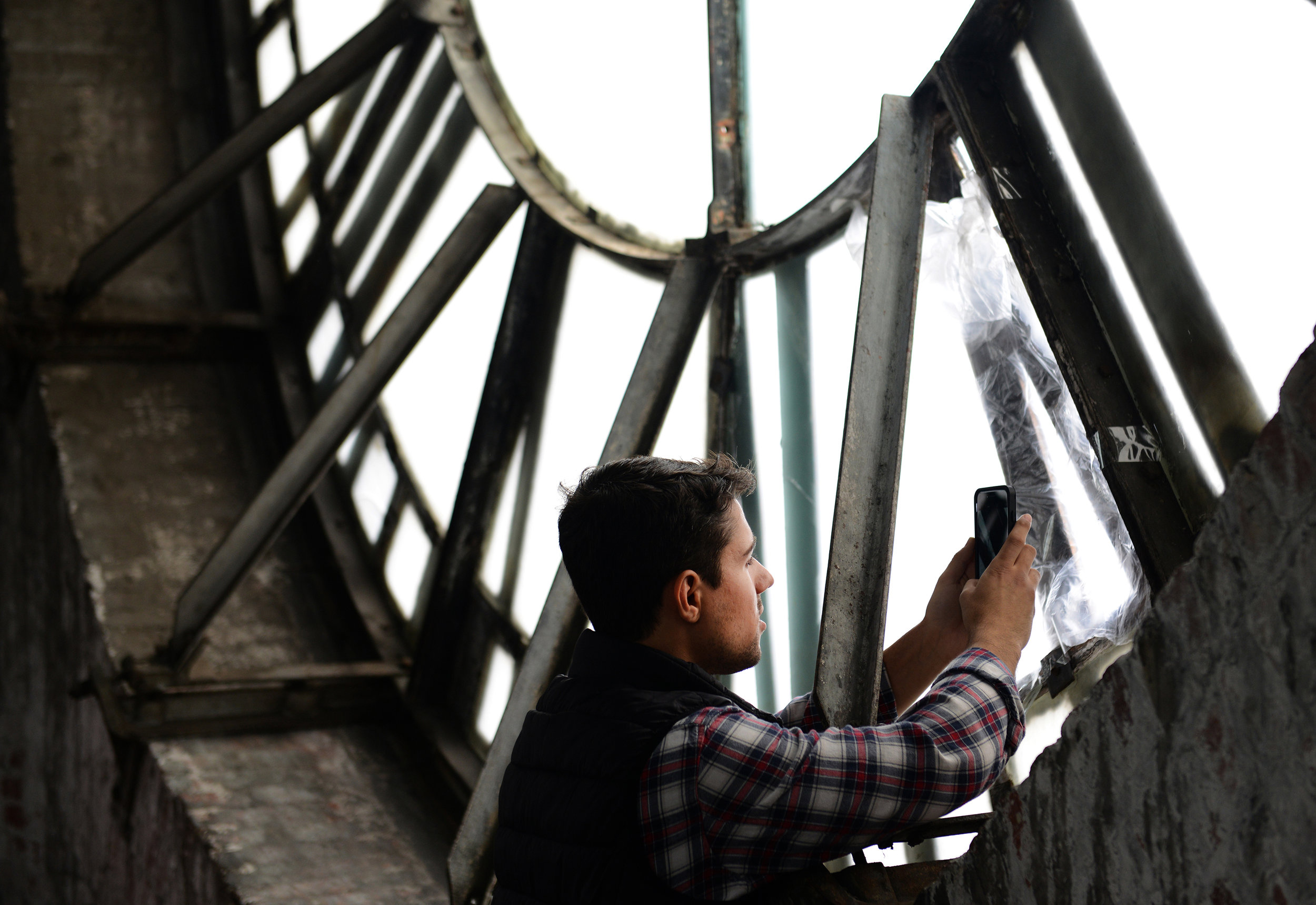 Johns Hopkins University student Bryan Ricciardi snaps a picture through a crack in the southern face of the clock while touring the Bromo Seltzer Arts Tower on Saturday, February 20, 2016 in Baltimore, Md. Photo by David Andrews.