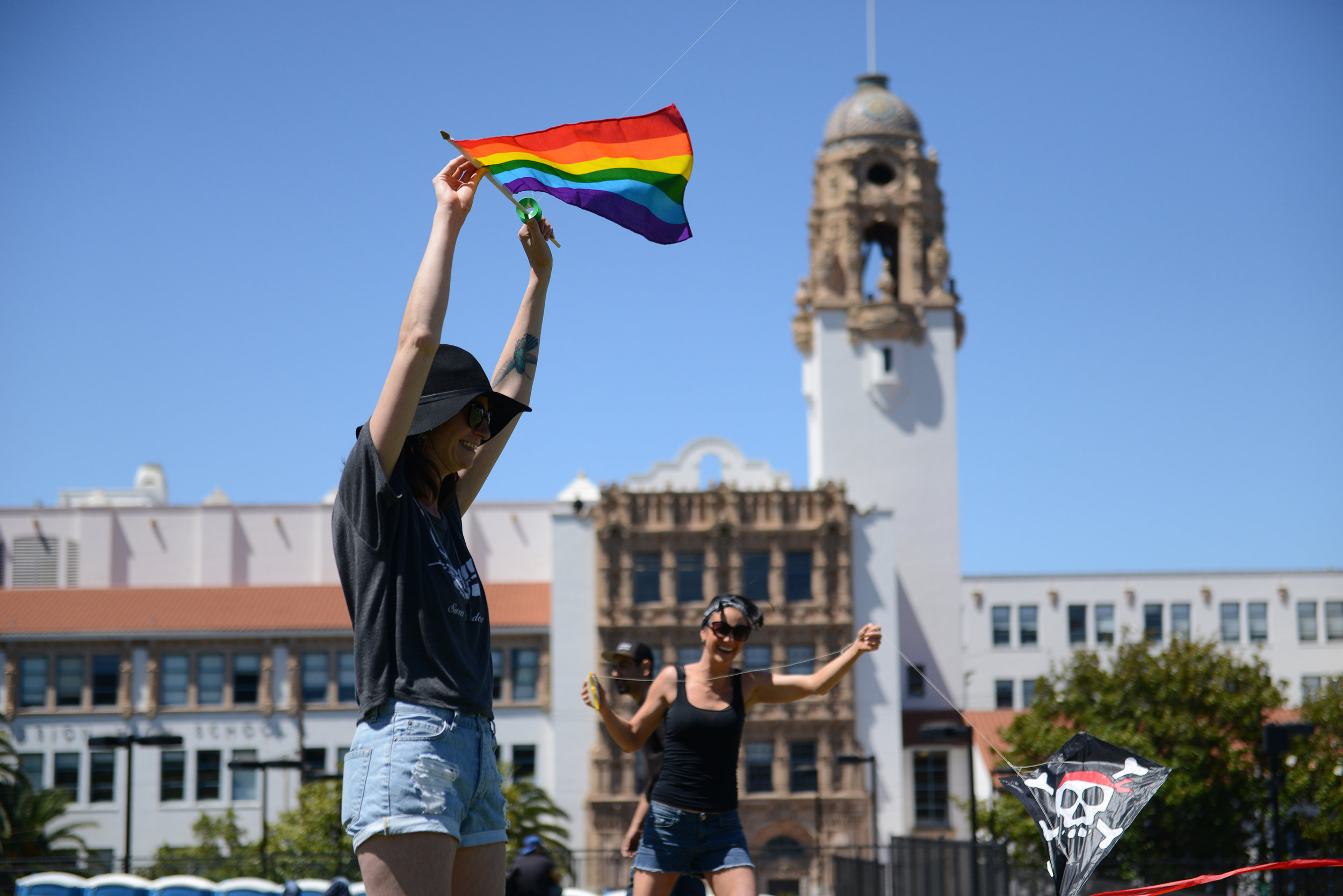 Krystal Barovetto, left, and her sister Dariann fly kites in front of Mission High School at Dolores Park in San Francisco, Ca. Krystal said they bought and were flying the rainbow flag in memory of a friend who recently passed. Photo by David Andrews.