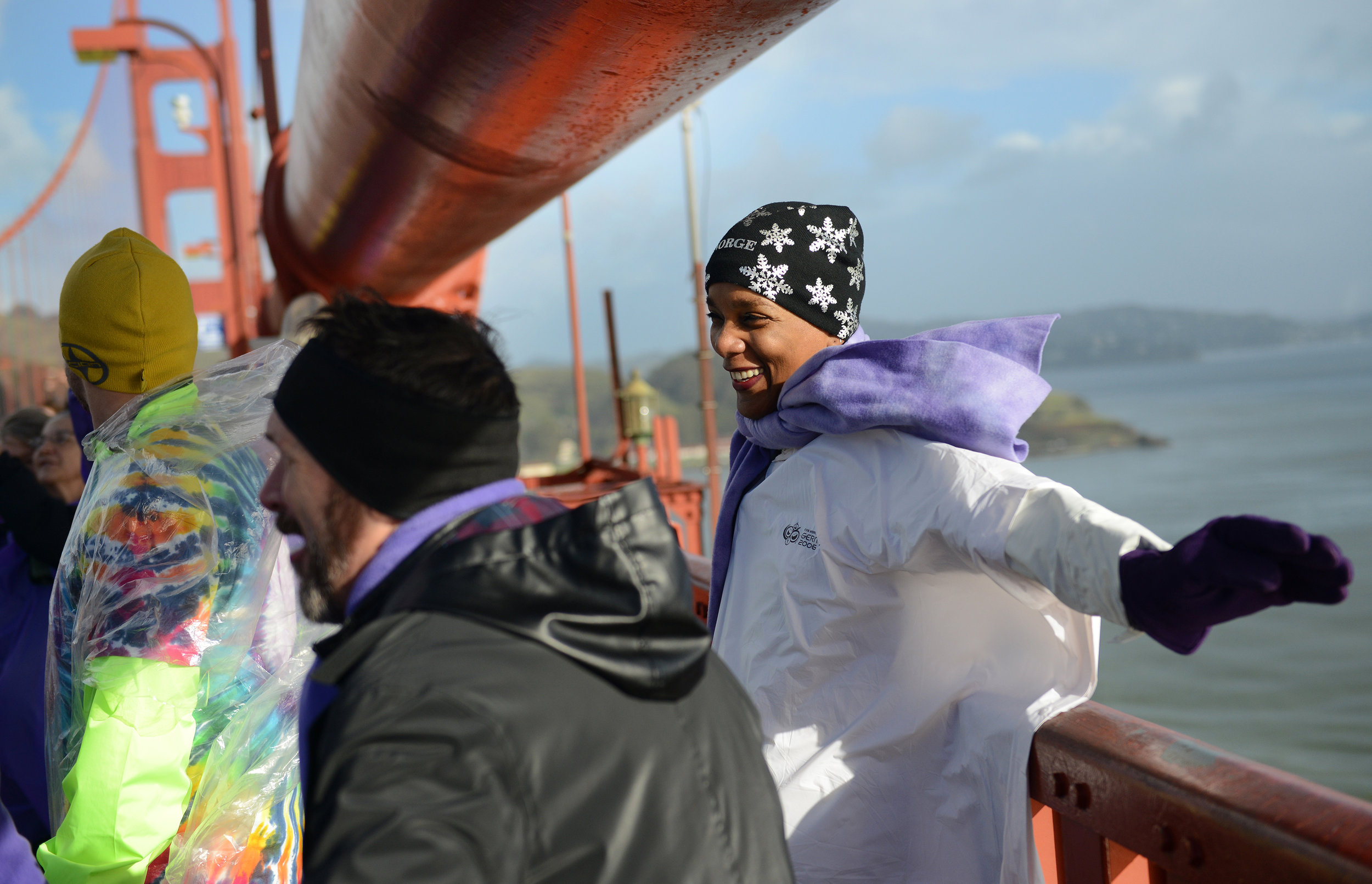 """June Solomon stretches her arms over the edge of the Golden Gate Bridge in San Francisco, Ca. on Friday, January 20, 2016 during a """"Bridge Together"""" demonstration. The event was coordinated by Satoriteller, a San Francisco art-based production studio to take place at the same time as the inauguration of President-elect Donald Trump to raise awareness for bullying and to take a stand against bullying rhetoric nationwide. Photo by David Andrews and is Property of Hoodline and Pixel Labs, Inc.  See more here ."""