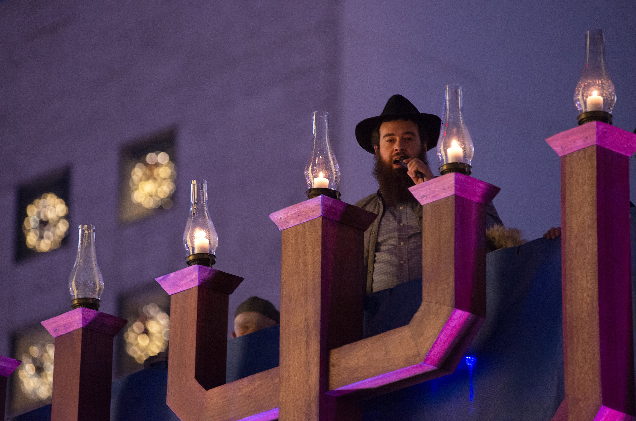 Rabbi Moshe Langer leads a crowd in the singing of holiday tunes atop the 25-foot-tall menorah in San Francisco, Ca. on December 6, 2018, the fifth day of Hanukkah. Rabbi Langer opened the celebration by lighting the massive menorah, which has illuminated San Francisco's Union Square each Hanukkah since 1975. Photo by David Andrews.