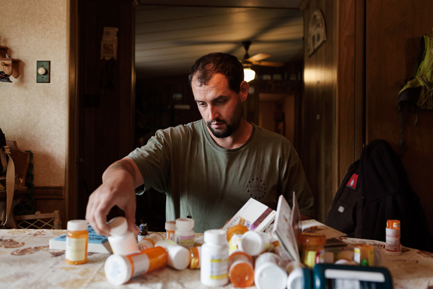 FARMER_VETERAN - U.S. Army veteran Alex Sutton sorts through the many prescription medications that he takes on a daily basis [websize].jpg