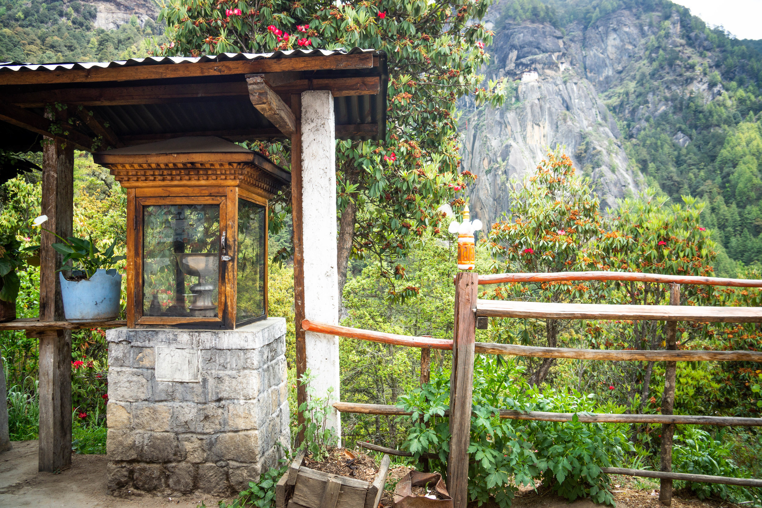 A view of the butter lamp with Tiger's Nest hanging on the cliffside behind it