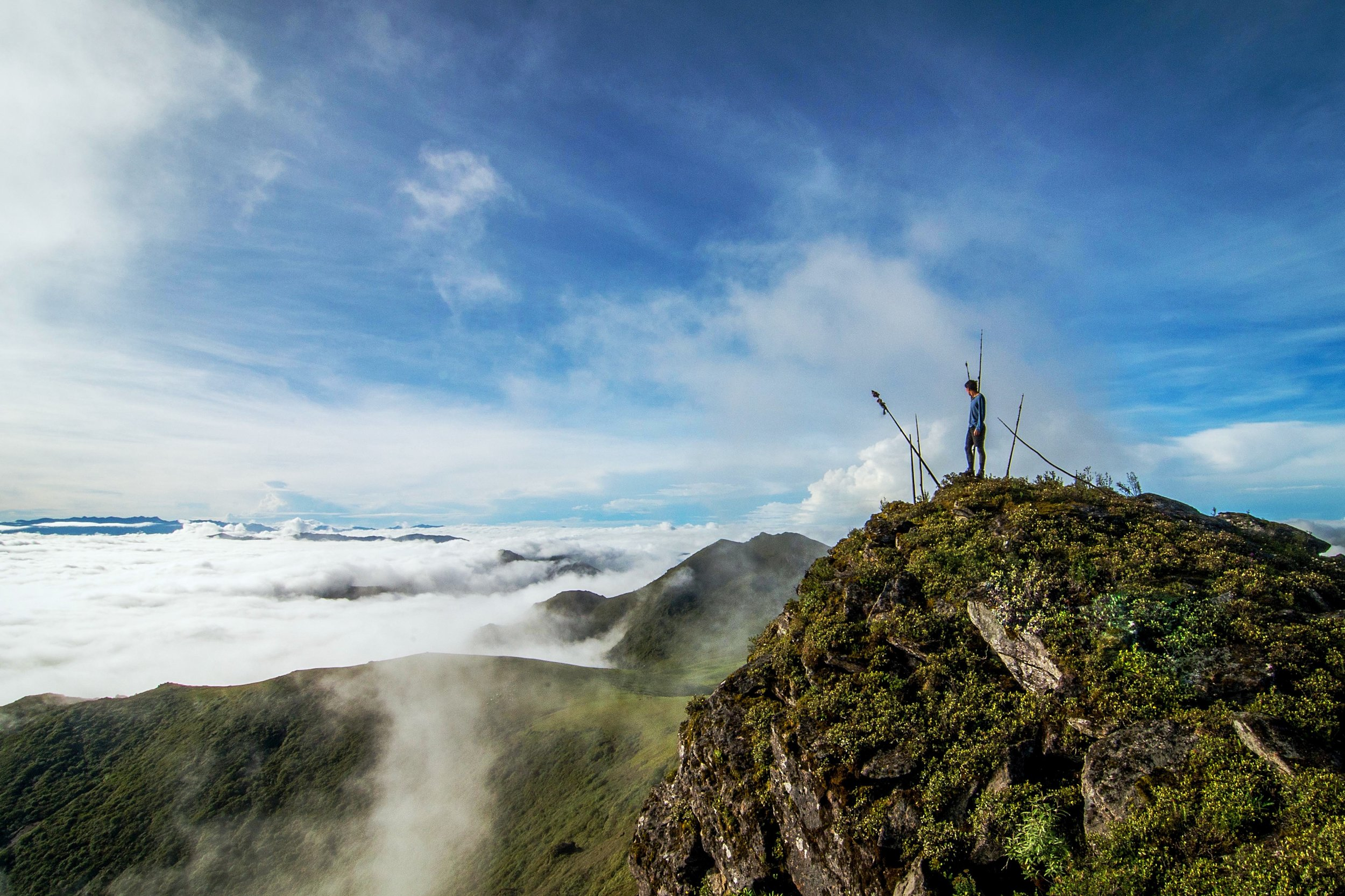 A man stands atop a ledge overlooking the clouds below him in northwestern Bhutan.