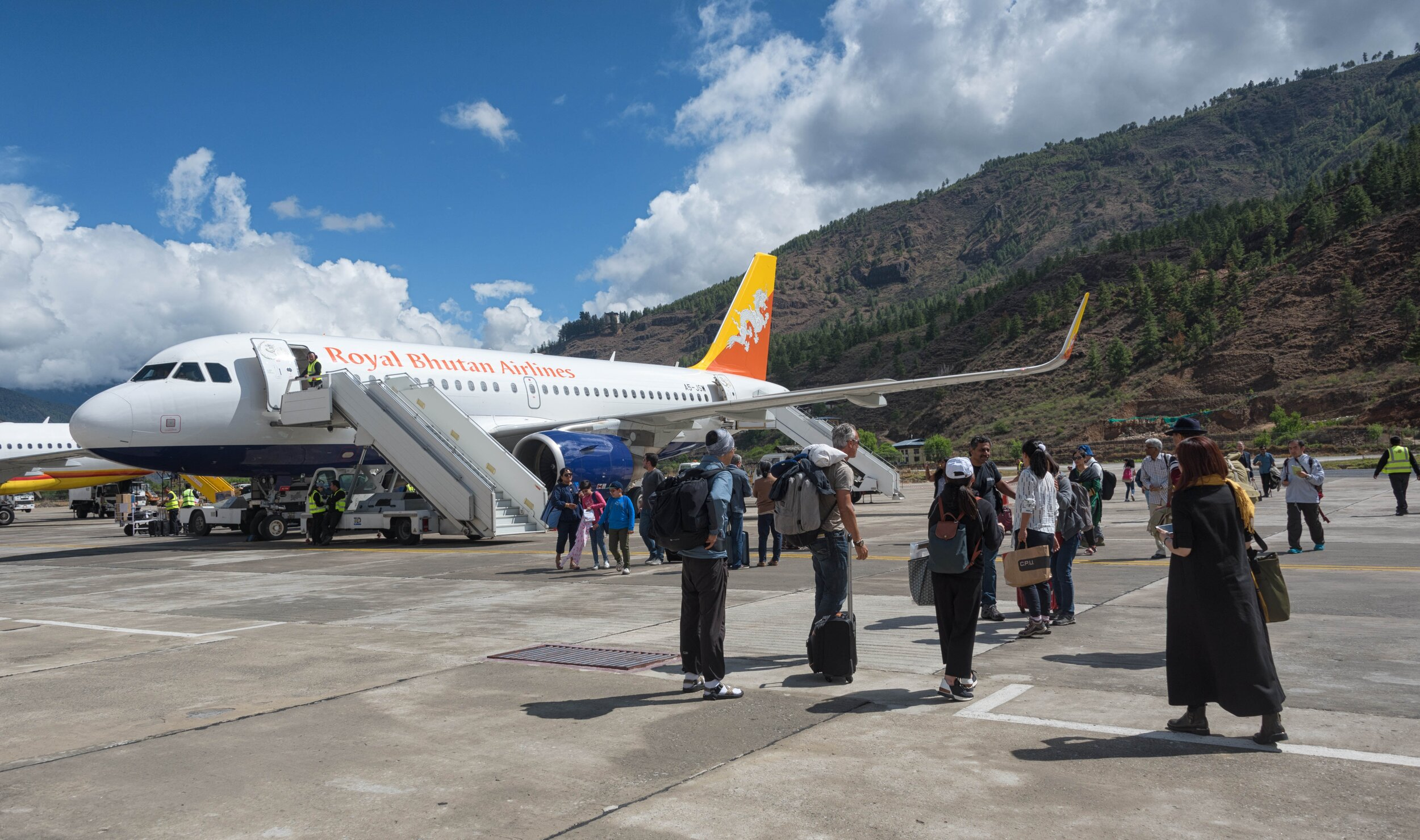 Travelers standing on the runway in awe of their surroundings after landing (PC: MyBhutan's DeSantis)