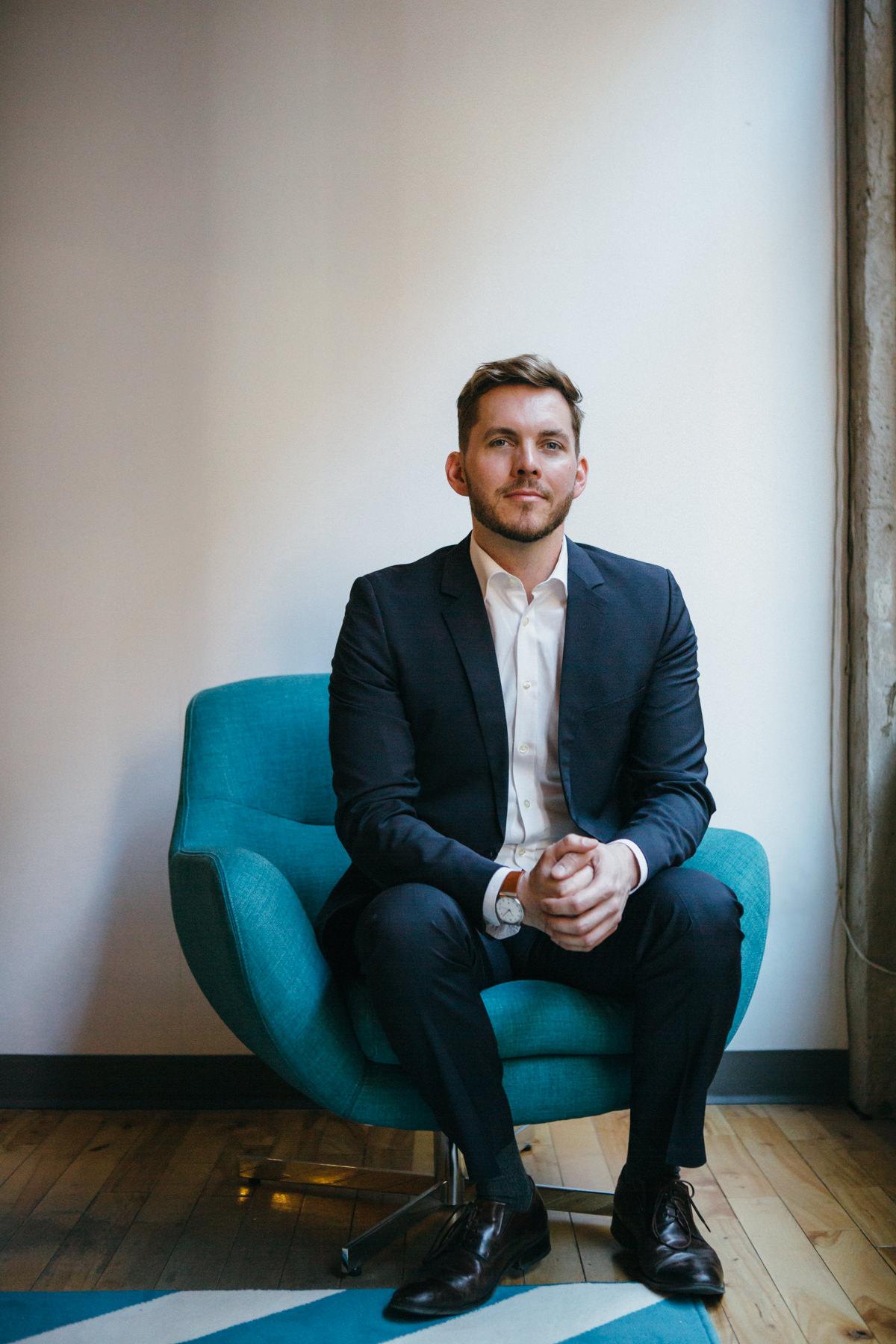 Lawyer Marcus McCann sits on blue chair beside window. Photo by Jocelyn Reynonds